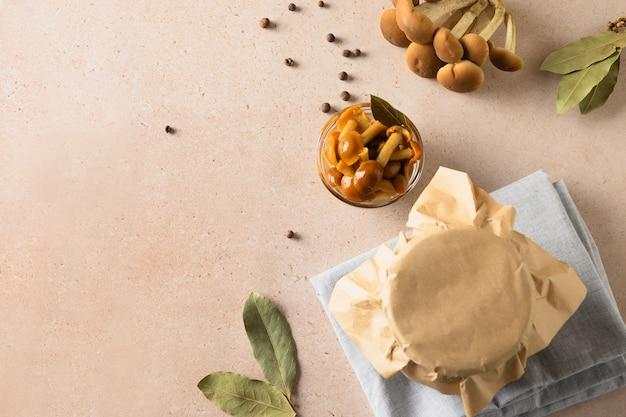 Marynowane grzyby miodowe podawane w misce z liściem laurowym
