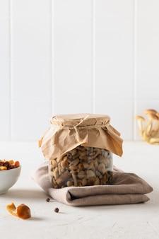 Marynowane grzyby miodowe w misce i słoiku na białym tle