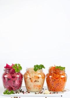 Marynowane i sfermentowane domowe warzywa. kapusta kiszona, marynowana czerwona kapusta i marchew w szklanych słoikach z miejsca na kopię