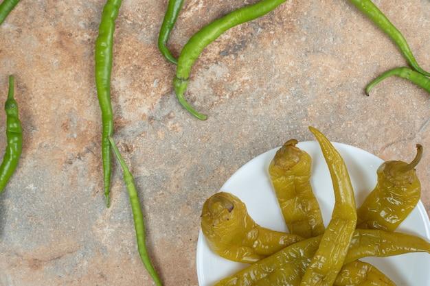 Marynowane i świeże zielone papryki na białym talerzu