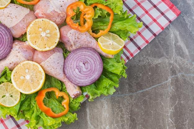 Marynowane mięso i warzywa na ściereczce, na marmurze.