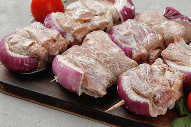 Marynowane mięso na szaszłykach z cebulą na szarym stole