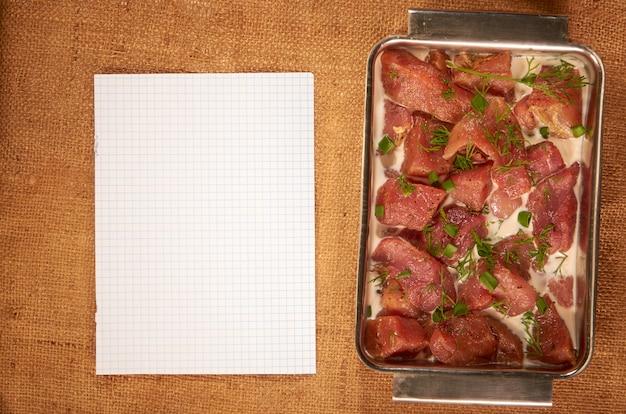 Marynowane mięso w mleku i zieleni w stalowym głębokim talerzu na domowej szmatce z czystą kartką papieru