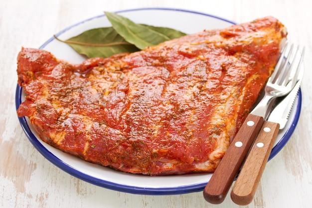 Marynowane mięso z widelcem i nożem na białym talerzu