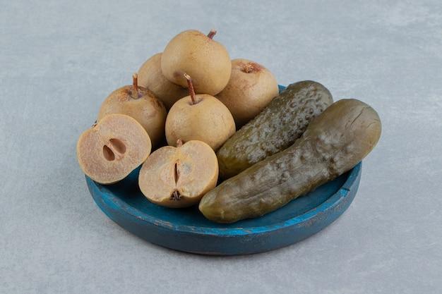 Marynowane ogórki i jabłka na drewnianym talerzu na marmurowej powierzchni