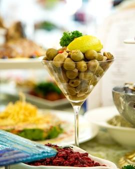 Marynowane oliwki zielone podawane w kieliszku koktajlowym zwieńczonym cytryną i ziołami