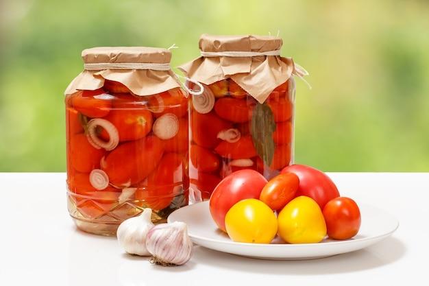 Marynowane pomidory w szklanych słoikach na naturalnym tle.