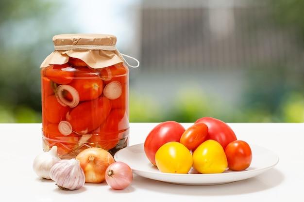 Marynowane pomidory w szklanych słoikach na niewyraźne tło.