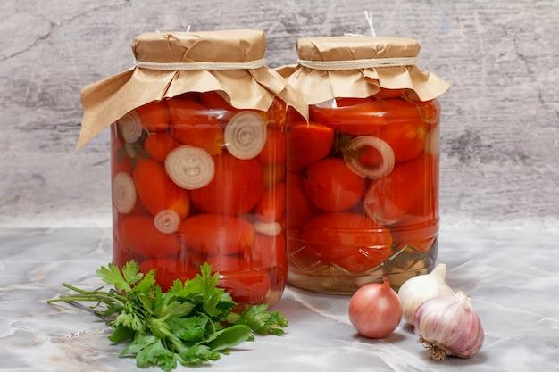 Marynowane pomidory w szklanych słoikach na stole w kuchni.