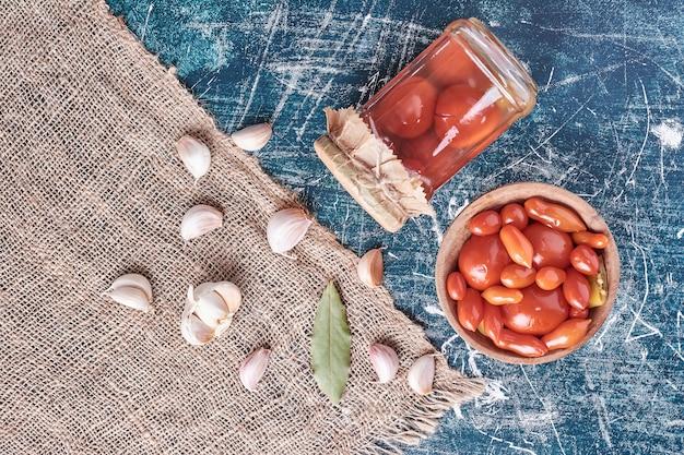 Marynowane pomidory w szklanym słoiku i misce z czosnkiem na niebiesko.