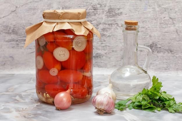 Marynowane pomidory w szklanym słoju na stole w kuchni.