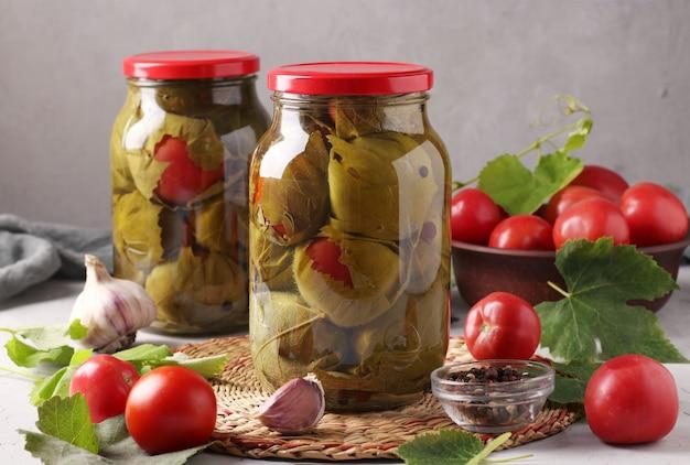 Marynowane pomidory z czosnkiem w liściach winogron w dwóch szklanych słoikach na szarej ścianie. zbliżenie. format poziomy
