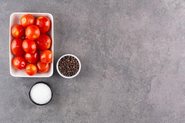Marynowane pomidory z ziarnami pieprzu ułożone na kamiennym stole.
