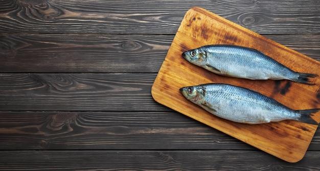 Marynowane ryby śledzia atlantyckiego na desce do krojenia
