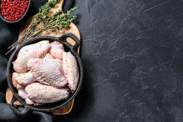 Marynowane skrzydełka z kurczaka z przyprawami i ziołami na patelni