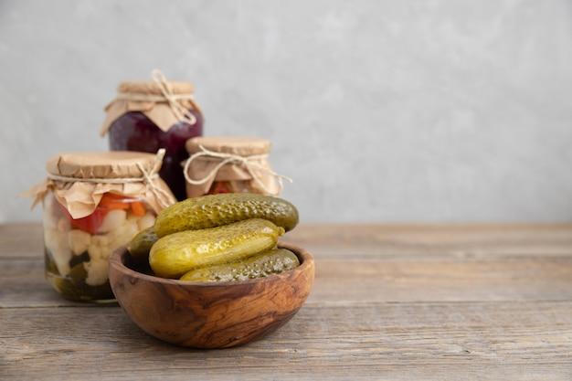 Marynowane, solone, fermentowane ogórki leżą w drewnianej misce na drewnianym stole.