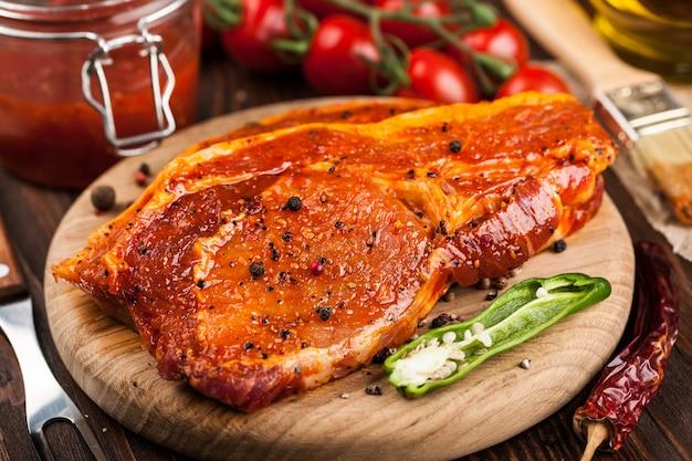Marynowane steki wieprzowe na desce do krojenia i składniki do gotowania