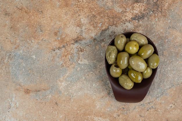Marynowane zielone oliwki w ciemnej misce