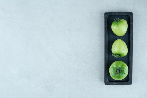 Marynowane zielone pomidory na czarnym talerzu.