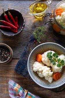 Marynowany kalafior z marchewką w szklanym słoju na ciemnym drewnianym stole. sfermentowane jedzenie. widok z góry