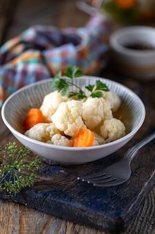 Marynowany kalafior z marchewką w szklanym słoju na ciemnym drewnianym stole. sfermentowane jedzenie.