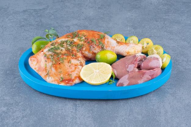 Marynowany kurczak i mięso na niebieskim talerzu.