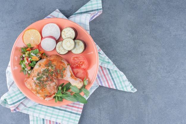 Marynowany kurczak i pokrojone warzywa na pomarańczowym talerzu.