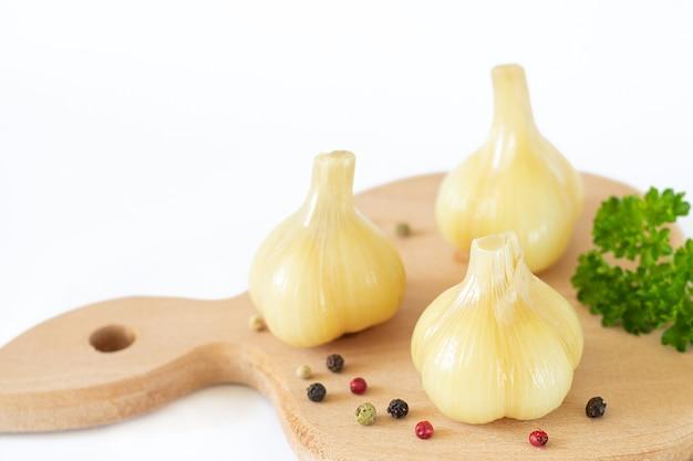 Marynowany sfermentowany zdrowy młody czosnek na desce. jedzenie zwiększające odporność