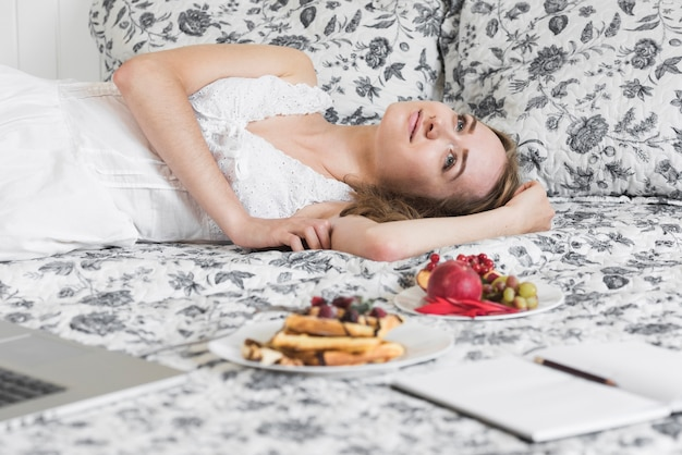 Marzący blondynki młodej kobiety lying on the beach na łóżku z zdrowym śniadaniem na łóżku