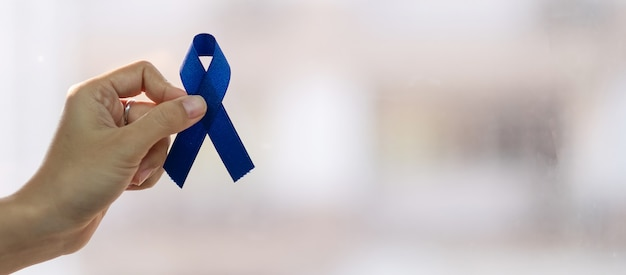 Marzec miesiąc świadomości raka jelita grubego, mężczyzna trzyma granatową wstążkę za wspieranie ludzi żyjących i chorych. koncepcja opieki zdrowotnej, nadziei i światowego dnia walki z rakiem