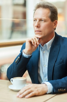 Marzenia biznesowe. rozważny dojrzały mężczyzna w stroju formalnym pijący kawę i trzymający rękę na brodzie siedząc w kawiarni