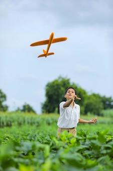 Marzenia o locie! indyjskie dziecko bawi się zabawkowym samolotem na zielonym polu