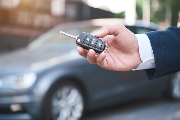 Marzenia się spełniają młody człowiek trzyma kluczyki do nowego samochodu