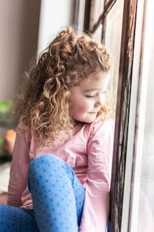 Marzenia się spełniają. piękna dziewczyna wyrażająca pozytywne nastawienie patrząc przez okno