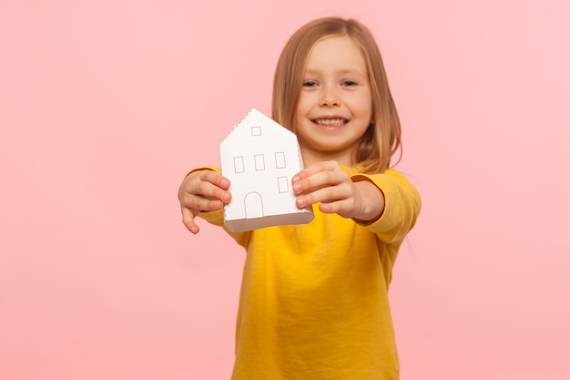 Marzenie o domu, ubezpieczenie. portret wesołej dziewczynki pokazano dom papieru i uśmiecha się do kamery, ogłoszenie nieruchomości, program niedrogich mieszkań. studio strzał na białym tle na różowym tle