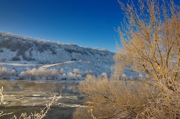 Marznąca rzeka z pagórkowatych brzegów i duże kry lodowe. słoneczny dzień z bezchmurnym niebem.