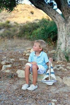 Marzy chłopiec siedzi pod drzewem i trzyma łódkę zabawki