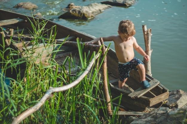 Marzy chłopiec w starej łodzi na wybrzeżu jeziora. ładny mały chłopiec siedzi w starej drewnianej łodzi na charakter.