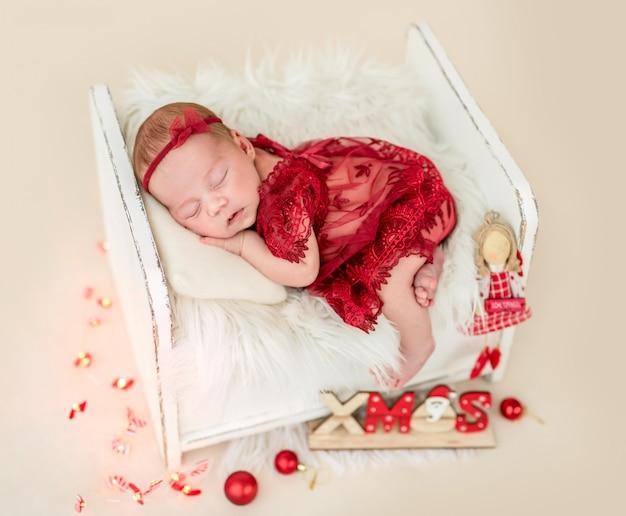 Marzy noworodka w małym łóżku