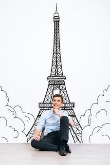 Marzy o paryżu. młody przystojny mężczyzna trzymając rękę na brodzie i odwracając wzrok z uśmiechem siedząc na podłodze z ilustracją wieży eiffla w tle