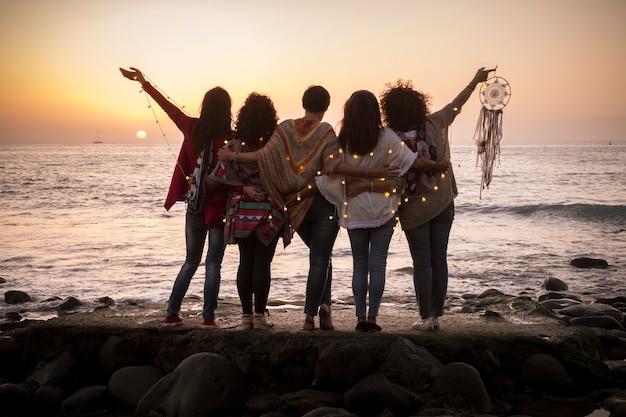 Marzy obraz z grupą przyjaciółek przytulają się wszyscy razem, patrząc na zachód słońca dla koncepcji przyjaźni i miłości - na zawsze przyjaciele i koncepcja stylu życia marzeń - ludzie cieszący się i czujący