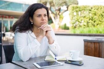 Marzycielska ładna kobieta relaksuje i siedzi w ulicznej kawiarni