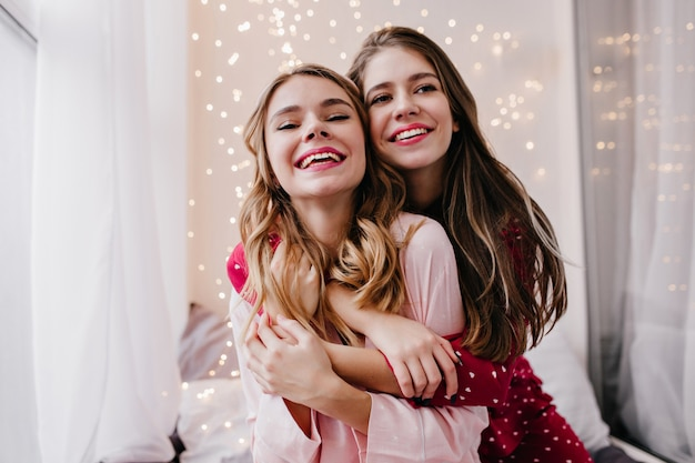 Marzycielska biała dziewczyna obejmująca siostrę i odwracająca wzrok z uśmiechem. wewnątrz zdjęcie chłodnych koleżanek pozujących w piżamie.