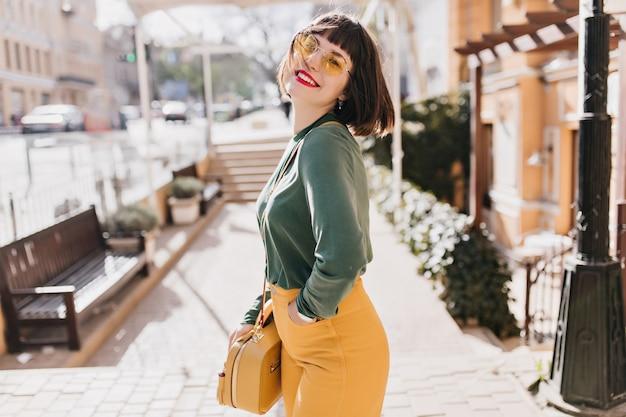 Marzycielska biała kobieta w modnej torebce śmiejąca się na miejskiej ulicy. plenerowe zdjęcie niesamowitej brunetki ze stylową fryzurą.