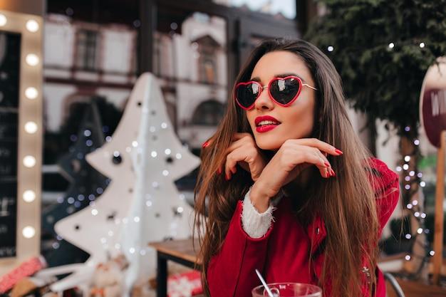 Marzycielska biała kobieta w modnych okularach przeciwsłonecznych serca chłodzi w kawiarni
