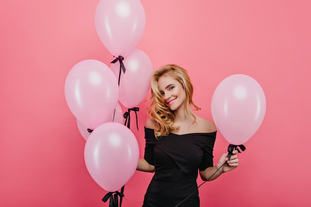 Marzycielska biała kobieta z śliczną twarzą, pozowanie na różowej ścianie z balonami. elegancka blond modelka obchodzi urodziny z imprezą.
