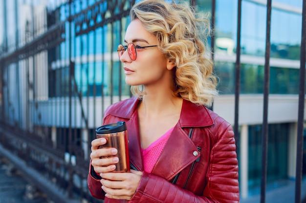 Marzycielska blond dziewczyna spacerująca po ulicach, pijąca kawę lub cappuccino. stylowy jesienny strój, skórzana kurtka i dzianinowy sweter. różowe okulary przeciwsłoneczne.