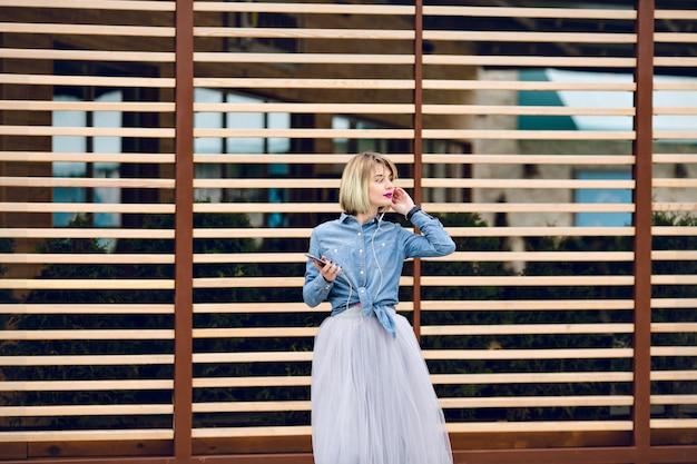 Marzycielska blondynka z jasnoróżowymi ustami stoi i słucha muzyki na smartfonie z pasiastymi drewnianymi belkami z tyłu