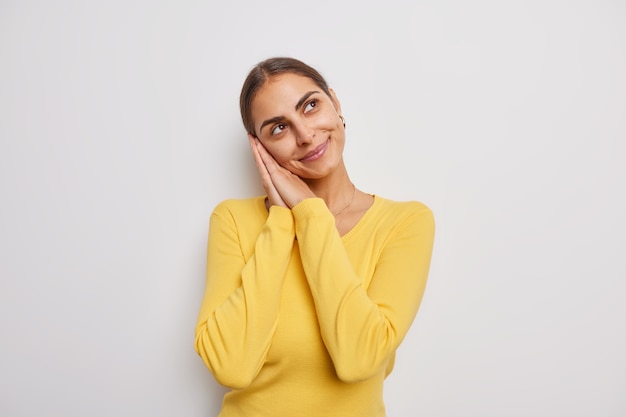 Marzycielska brunetka pochyla się na dłoniach z delikatnym wyrazem twarzy, myśli o czymś pozytywnym, nosi swobodny żółty sweter na białym tle nad białą ścianą