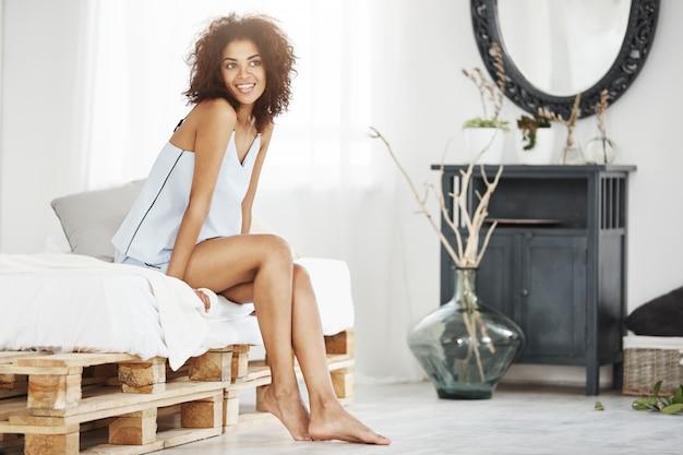 Marzycielska czuła afrykańska kobieta w piżamie siedzi na łóżku w ranku uśmiechniętym główkowaniu.